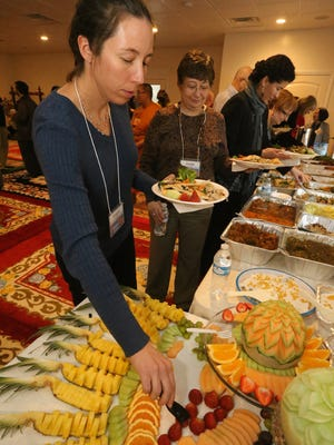 Laura Wells, left, gets some fresh fruit while in line, as Jayne Hasting, center and Vanessa Lazon get food during an Interfaith Community Lunch at the Buddhist Temple on Barfield Crescent Road on Friday, Jan. 15, 2016.