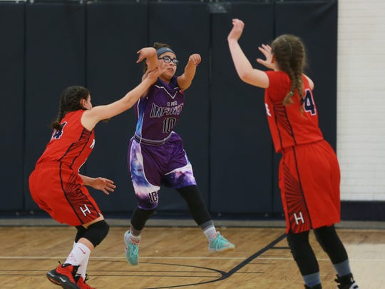 El Paso Infinity's Monique Moya, center, passes over Hustle's Isis Jimenez, left, and Iliana Vigil during a game at the Acosta Center. Teams are preparing to play in the upcoming regional basketball tournaments in El Paso.
