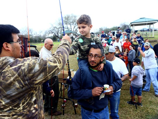 Dominic Ovalle, 5, grabs a free fishing rod from volunteer