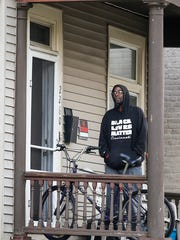 An unidentified man watches from his residence along Rice Street as CPD blocks off Rice and Valencia streets, Tuesday.