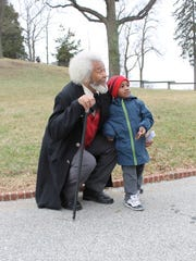 Jeremiah Moore, four years old, posing with Michael Crutcher Sr. dressed up as Frederick Douglass.