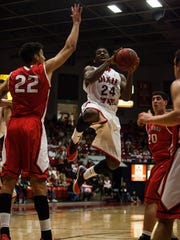Dixie State's DeQuan Thompson gets some air as he goes for two against BYUHawaii's DeAndre Medlock at the Burns Arena on Tuesday, Feb. 11, 2014.