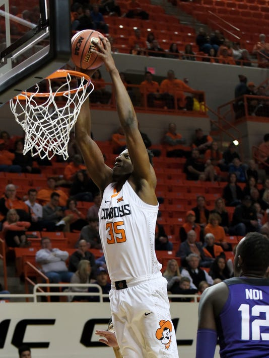 TCU forward Kouat Noi (12) watches as Oklahoma State forward Yankuba Sima (35) dunks in the first half of a NCAA college basketball game in Stillwater, Okla., Tuesday, Jan. 30, 2018.(AP Photo/Brody Schmidt)