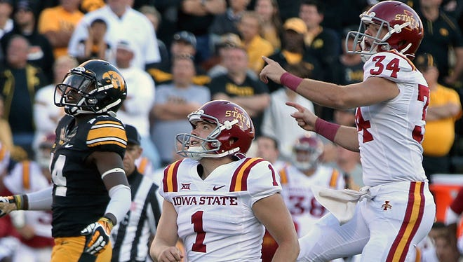 Iowa State kicker Cole Netten (1) and holder Austin Fischer, far right, watch the ball go through the uprights as they celebrate a victory at Iowa in 2014.