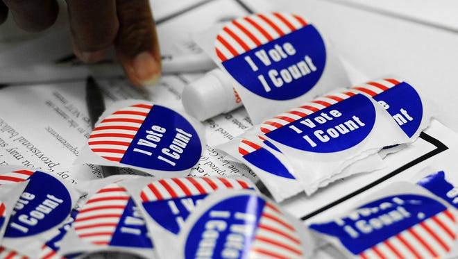People took advantage of early voting as voting stickers signify a ballot cast at the City County Clerks office on Monday, Oct. 8, 2012.