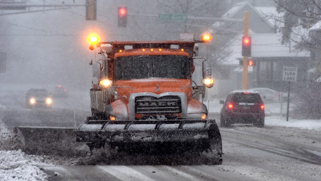 A snow plow clears a section of Veterans Drive. in St. cloud, Minn., on Nov. 18 as the season's firs tmajor winter storm rolled through the Midwest.