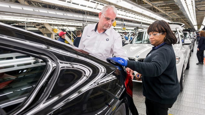 BMW Manufacturing President Knudt Flor works with associate Phyllis Thompson in Greer.