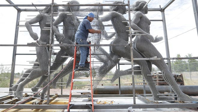 George Meraz of Industrial Stainless International works on a stainless-steel statue of five female figures running. It will be placed outside the new Sports Performance Center at Texas Tech University in Lubbock. The Chaparral, N.M., company has built several public art pieces for various cities.