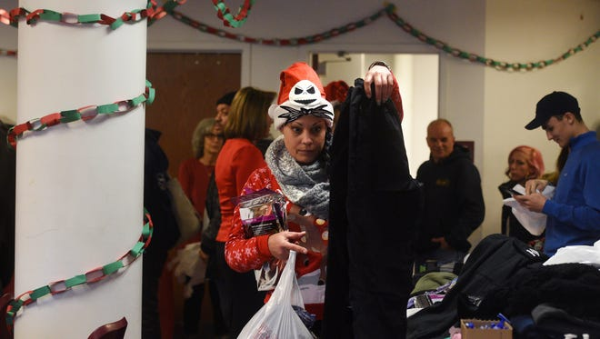 Julia Castro gathers clothing donations during Christmas lunch at the Housing, Health and Human Services Center in Hackensack on Monday afternoon. Castro and her husband, Pedro, have been staying at the shelter for 10 days.