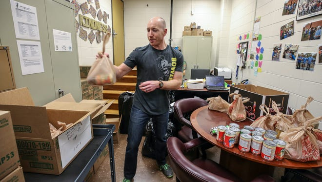 Family Resource Center coordinator Justin DeLorenzo prepares bags of food for Bowen Elementary students to take home as part of a Backpack Buddy program at the school that is made possible by Dare to Care Food Bank.December 12, 2017