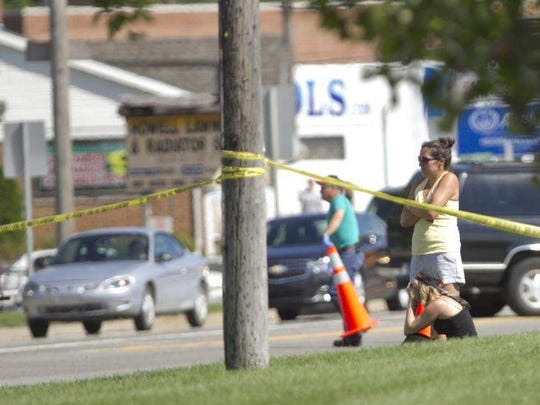 People stand along Grand River, stunned by the scene of a man lying in the road, shot fatally.