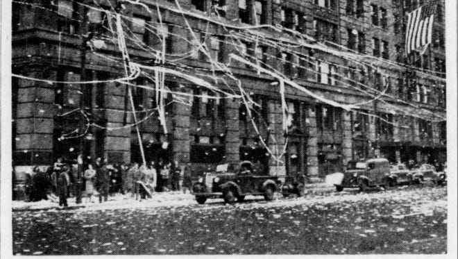 Ticker tape festoons overhead wires during a V-E Day celebration at Tenth and Market streets in Wilmington on May 8, 1945.