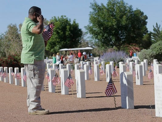 Kerry Pickett a retired Sgt First Class salutes one of the fallen soldiers. Pickett and others placed American flags on the headstones of soldiers buried at Fort Bliss National Cemetery.