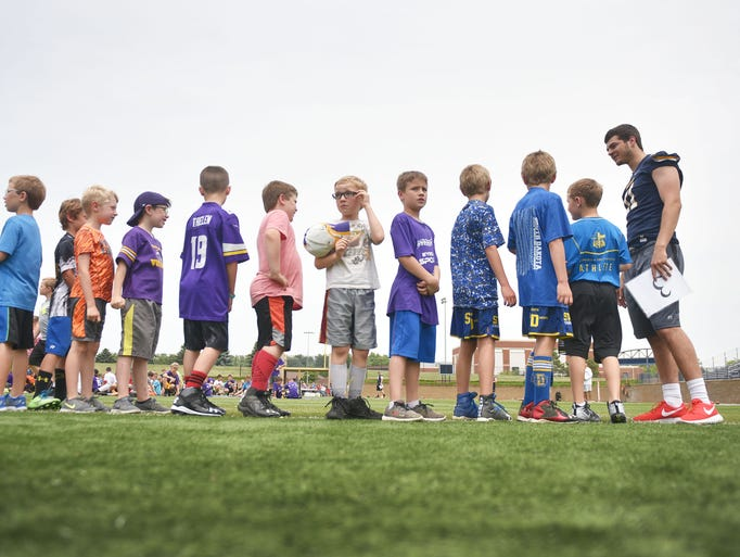 Kids line up with Augustana football players Friday,