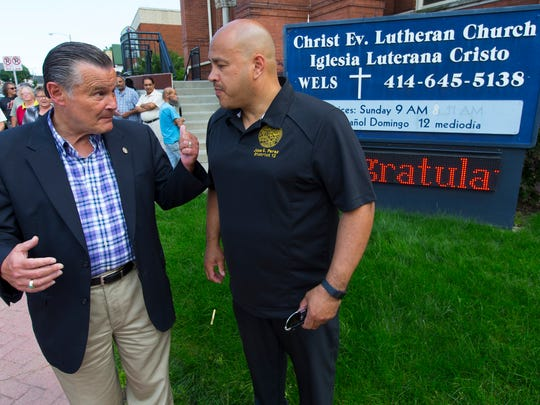 """Ald. Bob Donovan (left) speaks with fellow Ald. José G. Pérez Monday before a news conference outside Christ Evangelical Lutheran Church on W. Greenfield Ave. to discuss a lawsuit against the owners of a nearby home described as a """"hub of prostitution"""" on the city's near south side."""