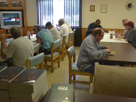 Some of the men who live at Transformation House in downtown Green Bay sit in the dining room to eat dinner and watch TV on Wednesday. Residents at the faith-based rooming house receive one meal a day during the week.