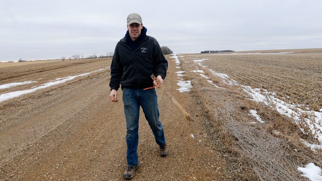 Aaron Johnson shows a wooden stake along his family's farm near Madison marking the proposed location of the Dakota Access pipeline.