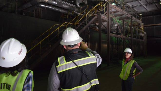 Lisa O'Brien of Leadership New Mexico's Core Program listens while San Juan Generating Station operating manager Heath Lee gives a tour of the plant on Thursday.