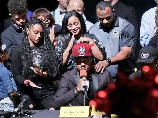 Patrick Surtain Jr., a defensive back at American Heritage High School, center, announces he is attending Alabama to play NCAA college football during a national signing day event, Wednesday, Feb. 7, 2018, in Plantation, Fla. At right is Surtain's father, Patrick Surtain Sr., the head football coach at American Heritage High School. (AP Photo/Lynne Sladky)