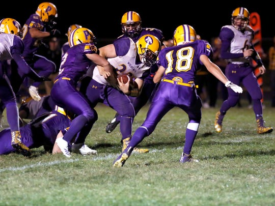 Pittsville's Tyler Dammann (2) tackles Wild Rose fullback Lucas Hackney as Brett Peters (18) arrives to aid in the tackle during their Central Wisconsin Conference-Small showdown Friday night.