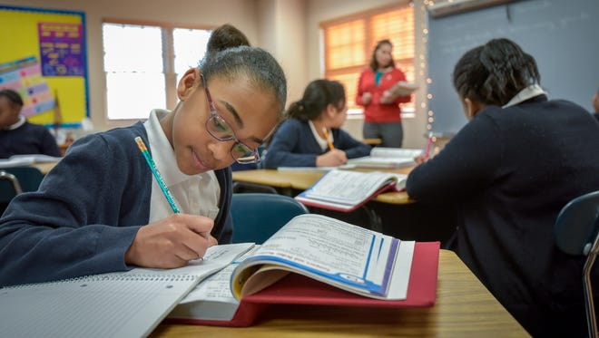 The Sisters Academy of New Jersey, Asbury Park, has thrived with minority girls for decades. Ariyana Perez (left) takes notes in her 6th-grade math class taught by Liz Potechko (in red).