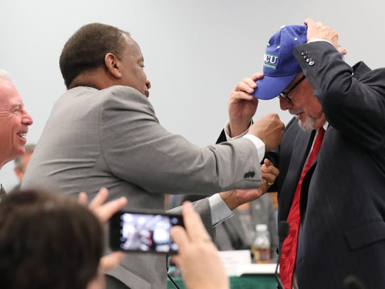 Current FGCU President Wilson Bradshaw congratulates Michael Martin on becoming the new FGCU President. Bradshaw reaches to put a pin on Martin's jacket as he puts an FGCU hat on. The Florida Gulf Coast University Board of Trustees voted to 12 to 0 to name Michael Martin, former chancellor at Louisiana State University, as the new president at Florida Gulf Coast University.