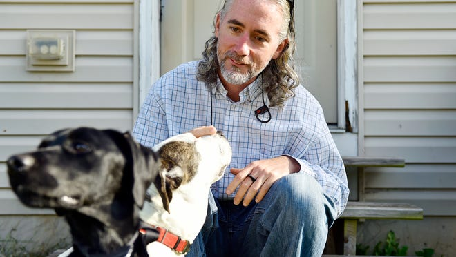 Budhi Blair relaxes with his dogs Ryder, left, and Layla, right, Thursday, Nov. 2, 2017, outside Blair's Windsor Township home. While serving 9 years in state prison, Blair joined a veterans' program where he learned to train rescue dogs. Blair, who said he endured childhood abuse and has PTSD from his service in Iraq, said working with dogs in the prison program helped him sleep at night and gain a new outlook on life after prison.