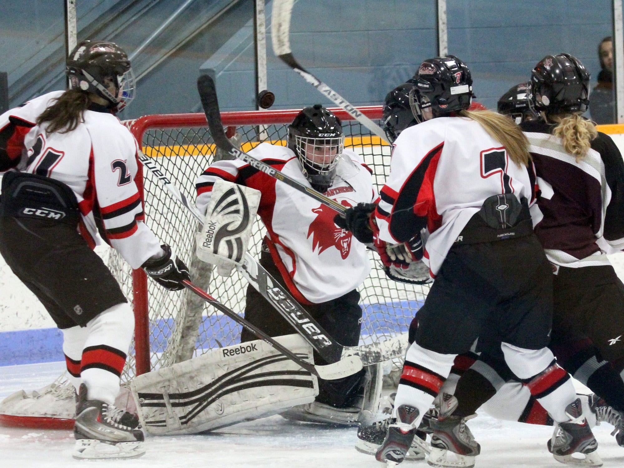 The puck pops up as Point/Rapids goalie Merina Chappel makes the initial save against the Central Wisconsin Storm during Friday's game at K.B. Willett Arena in Stevens Point.