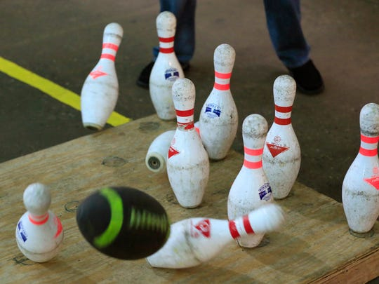 In a photo from June 19, 2015, in Hamtramck, Mich., a tossed football knocks over bowling pins during a game of Fowling.