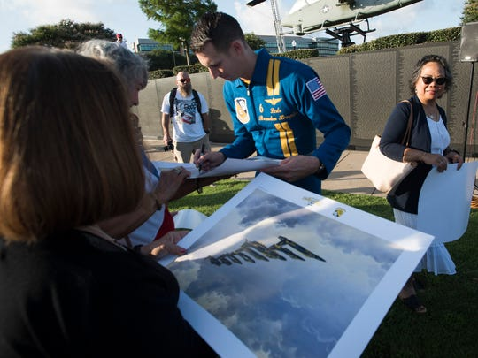Lt. Cmdr. Brandon Hempler, the Blue Angels opposing solo pilot, signs autographs for fans during Tuesday's, July 3, 2018, Blues in the City event at Veterans Memorial Park.