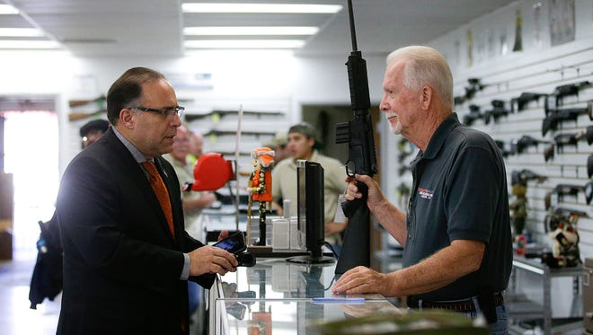 In this Dec. 9, 2015, photo, sales associate Mike Conway, right, shows Paul Angulo a semiautomatic rifle at Bullseye Sport gun shop in Riverside, Calif.