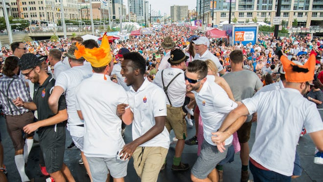 Players and coaches of FC Cincinnati dance with crowd of people during Oktoberfest at the corner of Elm and Second streets for the world's largest chicken dance Sunday September 18, 2016.