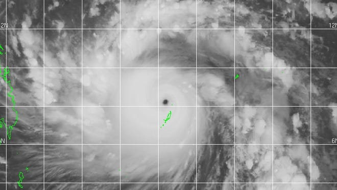 A satellite image shows Super Typhoon Haiyan spinning in the western Pacific as it moves west toward the Philippines (at the left in the green outlines).