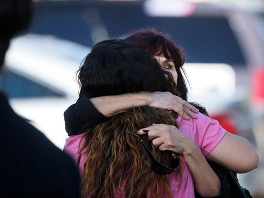 Teresa Hernandez, facing camera, is comforted by a