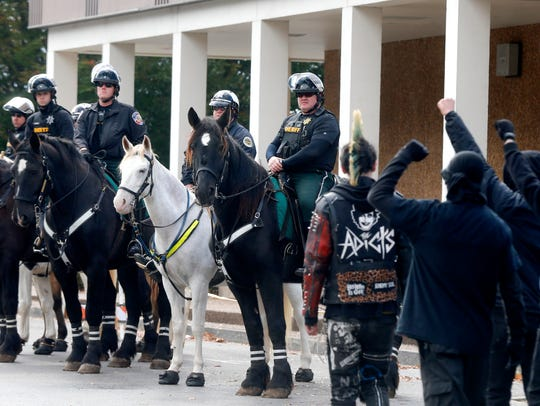 Law enforcement officers watch from horseback as Antifa