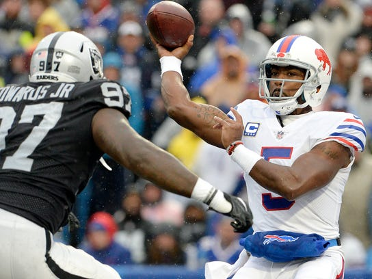 Buffalo Bills quarterback Tyrod Taylor (5) throws a pass as Oakland Raiders defensive end Mario Edwards (97) rushes in during the first half of an NFL football game, Sunday, Oct. 29, 2017, in Orchard Park, N.J. (AP Photo/Adrian Kraus)