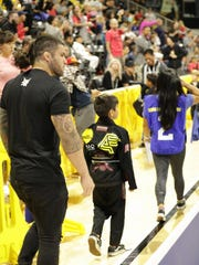 Mike Carbullido walks one of his students, Frankie Zambada, out to the mats before coaching him during his matches.