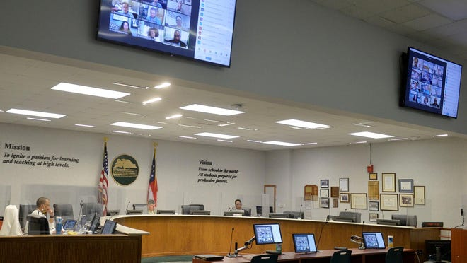 School Board President Joe Buck and Superintendent Ann Levet lead the Savannah-Chatham County School Board meeting from the Whitney Administrative Complex while other attended via the computer.