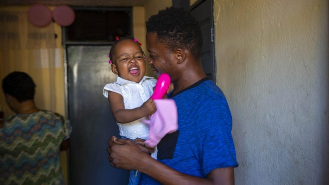 Verty, 30, holds his 1-year old daughter at his house in Port-au-Prince, Haiti, on Tuesday after being deported from the U.S.