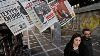 A couple walks near a kiosk selling newspapers depicting Alexis Tsipras, leader of radical leftist Syriza party, a day after the general elections in Athens, Greece. Tsipras is scheduled to be sworn in as prime minister in the afternoon. (EPA/YANNIS KOLESIDIS)