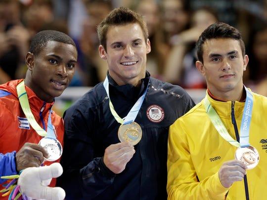 The United States' Sam Mikulak, center, holds his gold