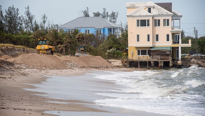 Crews work to build up the dunes at Bathtub Beach on Oct. 23, 2017, in Martin County after erosion from high tides, strong wind and heavy surf.