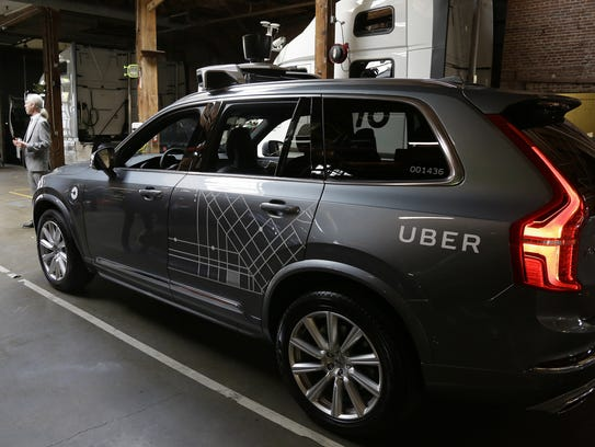 An Uber driverless car is displayed in a garage in