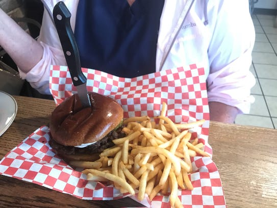 The Spicy River Burger is dunked in Franks Hot Sauce,