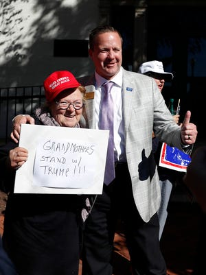"""Corey Stewart, chairman of Republican presidential candidate Donald Trump's Virginia campaign, right, gives the thumbs-up as he poses for a photo with Trump supporter Heidi Saba on Oct. 10, 2016. Her sign, which reads """"Grandmothers Stand w/Trump!!!"""" was part of a protest outside Republican National Committee Headquarters in Washington, and Stewart was fired later that day for organizing it."""