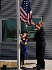 Keelee Cherry, 8, and Abilene Fire Department Capt. Steve Taylor raise an American flag for the first time during the dedication of the new Station 7 on North Pioneer Drive. Keelee, a second-grade student at Allie Ward Elementary School, was given the honor thanks to a poster she created.