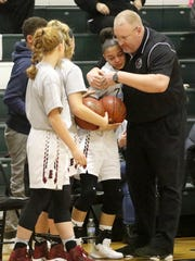 Elmira girls varsity coach Jake Dailey hugs Kiara Fisher after a moment of silence was held Monday in honor of Fisher's dad, Delmar Fisher, who died last year of complications from diabetes.