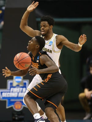 Michigan guard Derrick Walton Jr. defends Oklahoma State guard Jawun Evans during the first half of a first-round NCAA tournament game March 17, 2017 in Indianapolis.