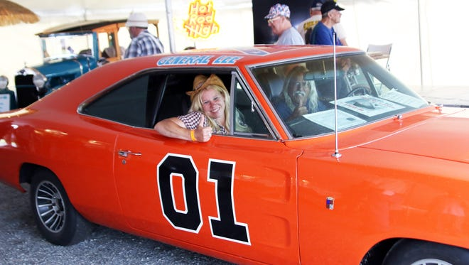 Dawn Hamilton and Steve Hopkins give a thumbs up while sitting in the General Lee.Holly Neumann photo.
