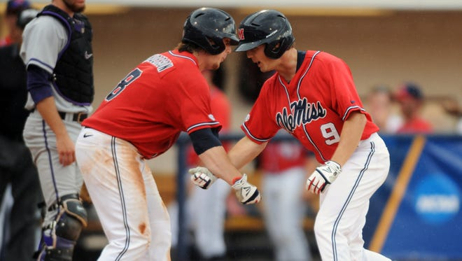 Mississippi's Auston Bousfield (9) celebrates his solo home run with teammate Austin Anderson as Washington's Austin Rei, left, looks on during their NCAA college baseball regional tournament game at Oxford-University Stadium on Sunday, June 1, 2014, in Oxford, Miss. Mississippi won 2-1. (AP Photo/Oxford Eagle, Bruce Newman) NO SALES.